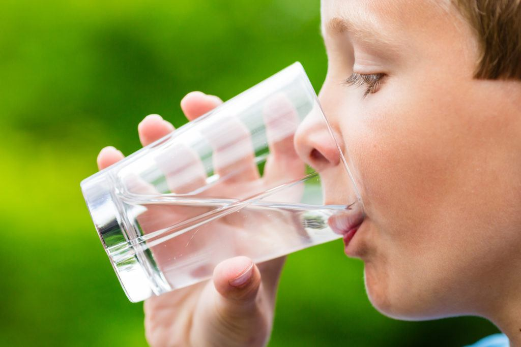 Close-up of young scandinavian child drinking fresh and pure tap water from glass with a blurred green background.